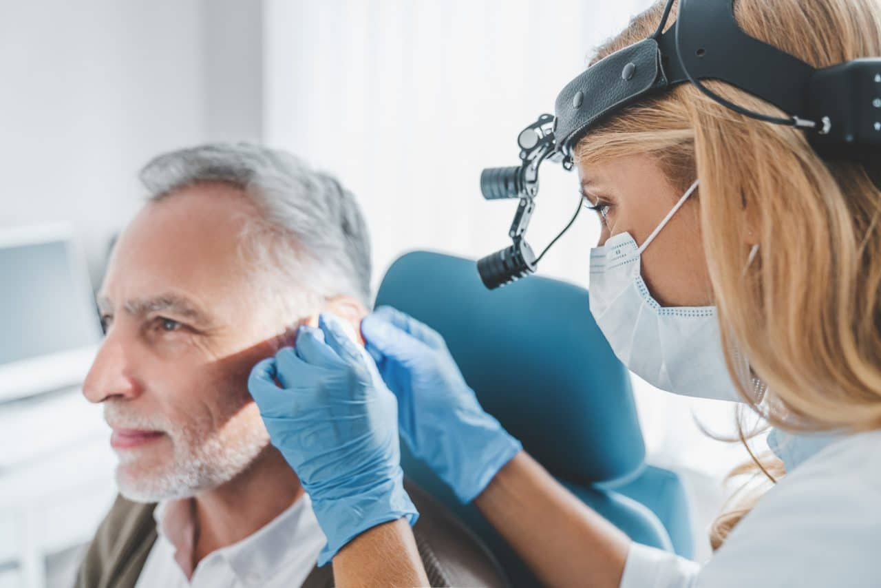 Audiologist examining patient with hearing loss.